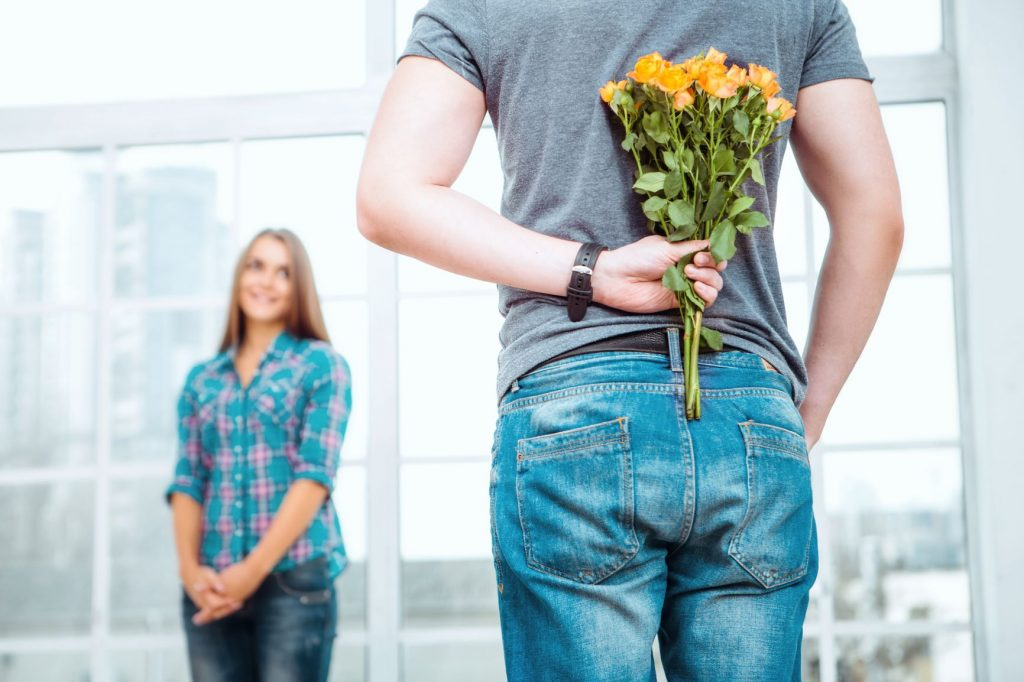 A man surprises a woman with flowers.