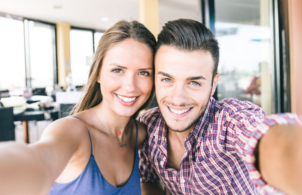 A young woman and a young man smile while taking selfies together.