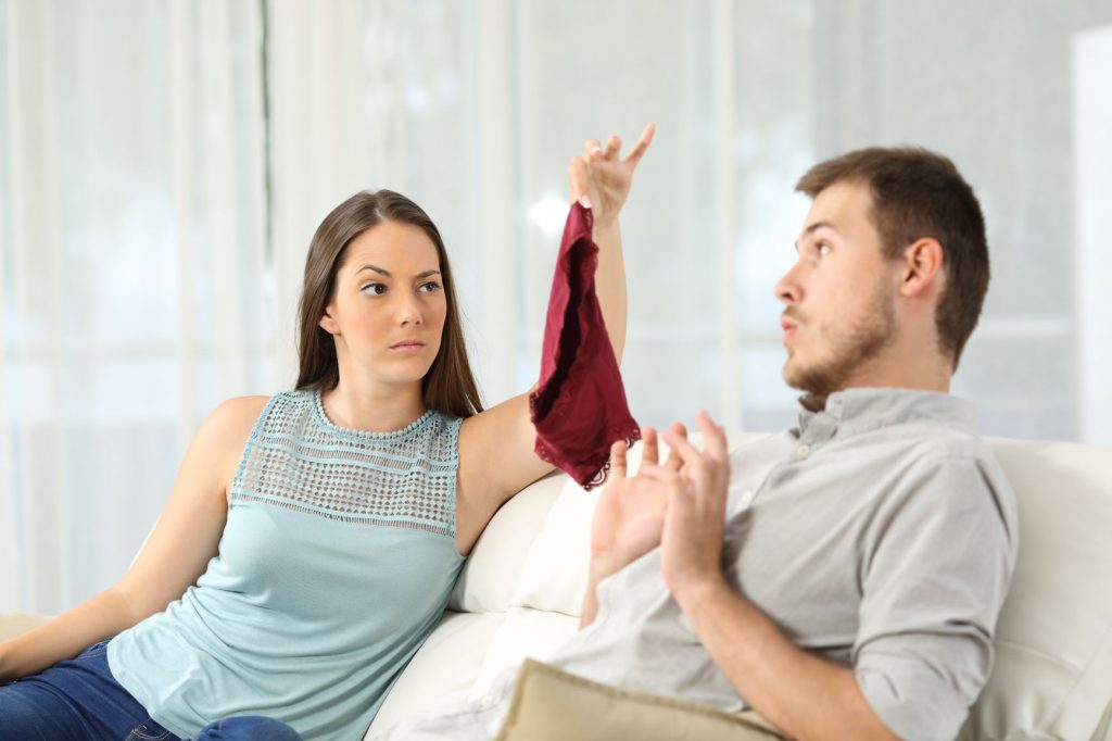 A young woman holds up an undergarment in front of a young man sitting on a sofa.