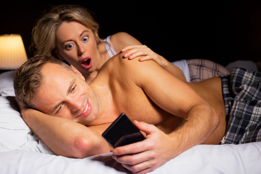 A woman sees her partner texting somebody else while they are in bed.